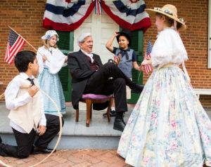 Costumed reenactors gather around a reenactor portraying James Buchanan.